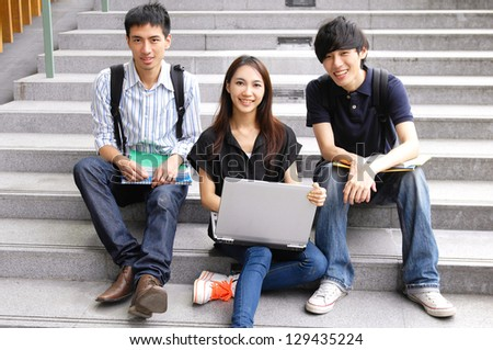 college friends sitting holding laptop with books on campus - stock photo