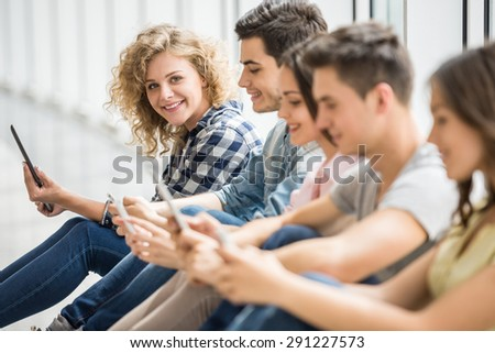 College friends sitting on the floor and watching pics on their gadgets at break. Side view.