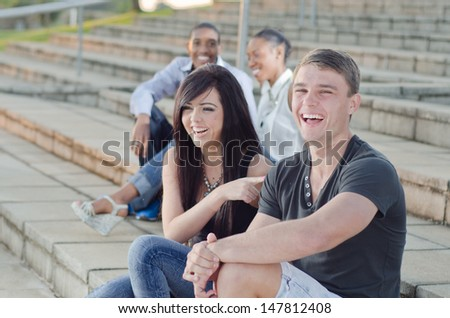College Friends sitting togther having a convertasion outside - stock photo