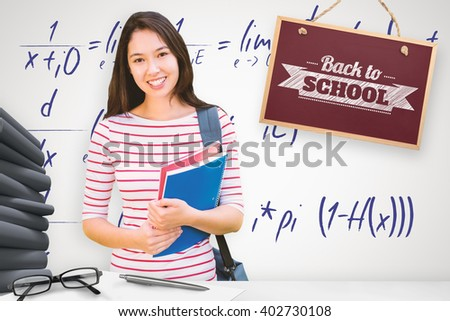College girl holding books with blurred students in park against grey background - stock photo