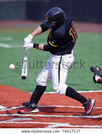 COLLEGE PARK, MD - APRIL 2: University of Maryland infielder Ryan Holland connects with a pitch during a game against #7 Florida State April 2, 2011 in College Park, MD. - stock photo