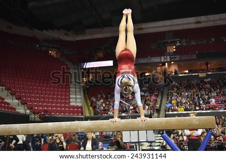COLLEGE PARK, MD - JANUARY 9: A Maryland gymnast competes on the balance beam during a meet January 9, 2015 in College Park, MD.  - stock photo
