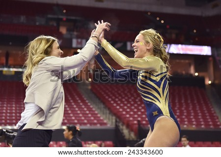 COLLEGE PARK, MD - JANUARY 9: WVU gymnast Melissa Idell is congratulated by a coach following a strong balance beam performance during a meet January 9, 2015 in College Park, MD.  - stock photo