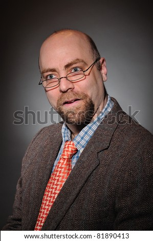 College Professor with a tweed coat and an orange tie over a gray background - stock photo