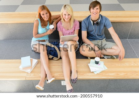 College student friends relax during break with tablet and books - stock photo