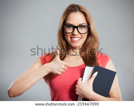 College student giving thumbs up to learning - stock photo