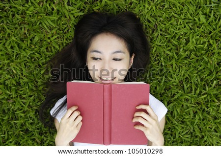 College student lying on the grass on campus - stock photo