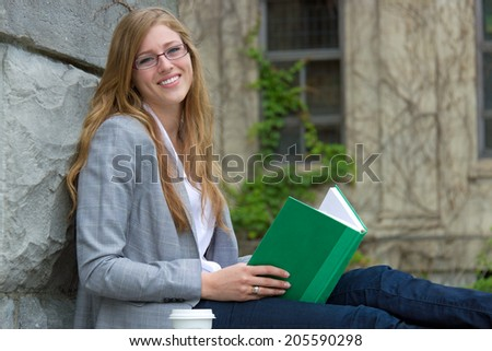 College student reading a book outdoors - stock photo