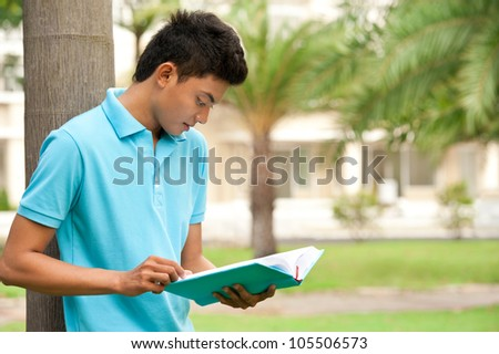 College student reading book near the university