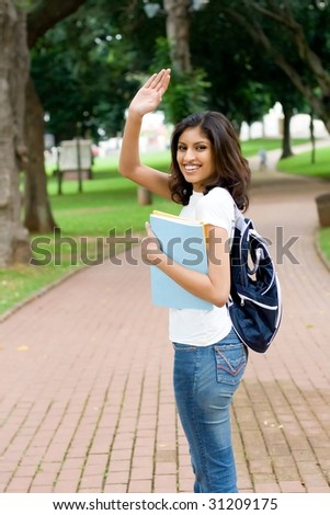 college student saying good bye and waving to her friend