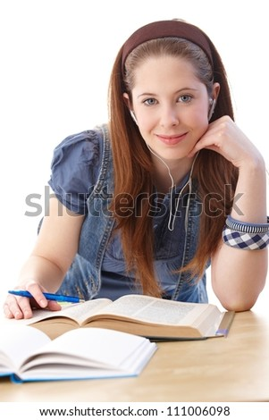 College student sitting at desk, learning, smiling at camera. - stock photo