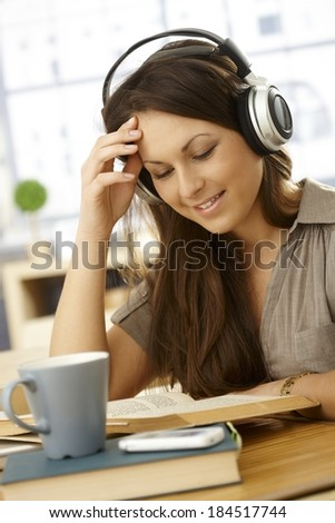 College student sitting at table at home, learning, using headphones, smiling. - stock photo