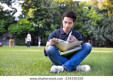 college student sitting holding book at college - stock photo