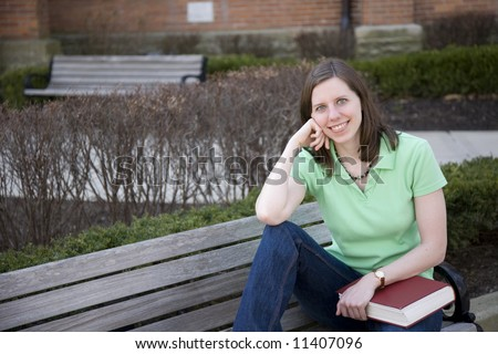 College student sitting on a bench on campus - stock photo