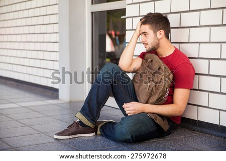 College student sitting outside a classroom with a hand on his hair, feeling stressed and upset about his grades - stock photo