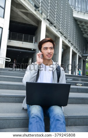 college student sitting use mobile phone in her hand at campus - stock photo