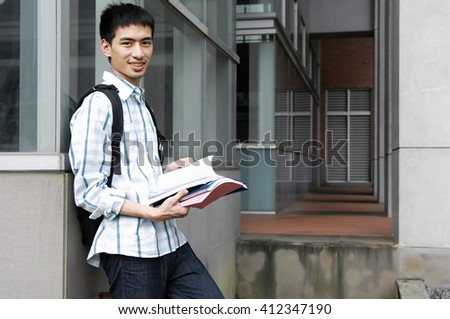 college student standing holding book at his university - stock photo