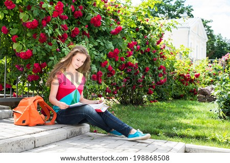College student studying at campus near roses bush. Preparing to exams outdoors. - stock photo
