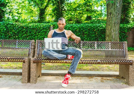 College Student Studying in Summer in New York. Wearing black, white striped tank top, jeans, red sneakers, an African American guy sitting on chair on campus, reading, working on laptop computer.  - stock photo