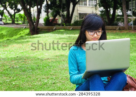 College Student using computer in university park outdoor