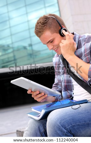 College student using digital tablet and headphones - stock photo