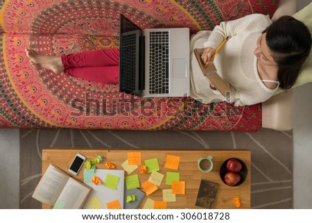 College student using laptop and making notes while studying at home - stock photo