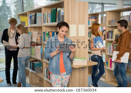 College student using tablet with classmates chatting in library - stock photo