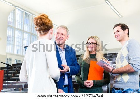 College students making lesson notes while asking professor in university auditorium - stock photo