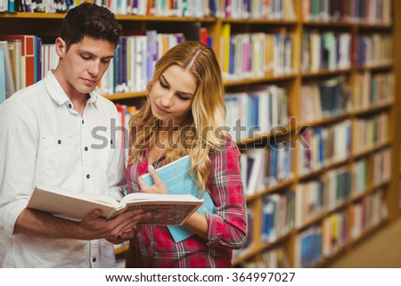 College students reading book together in library