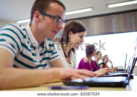 college students sitting in a classroom, using laptop computers during class (shallow DOF) - stock photo