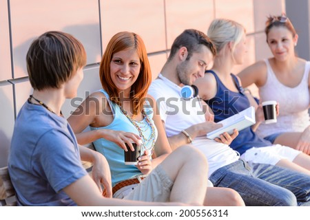 College students sitting in row modern wall outside summer campus - stock photo