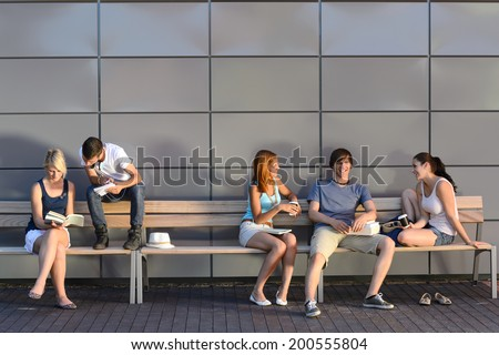 College students sitting on bench by modern wall outside campus - stock photo