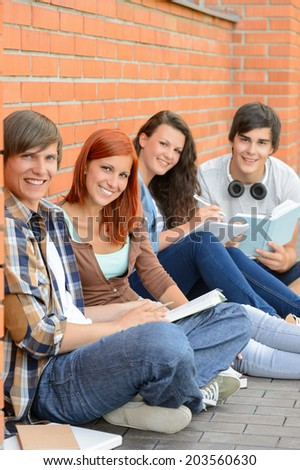 College students sitting on ground against brick wall holding books - stock photo