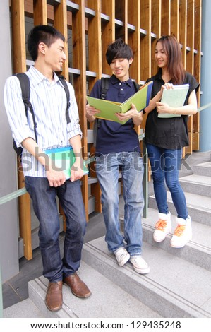 college students standing together with books at a campus