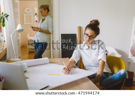 College students working together on blueprints at home