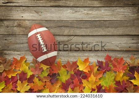 College style football on fall leaves and rough wood top view - stock photo