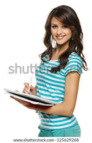 College university student woman making notes in the notebook, over white background - stock photo
