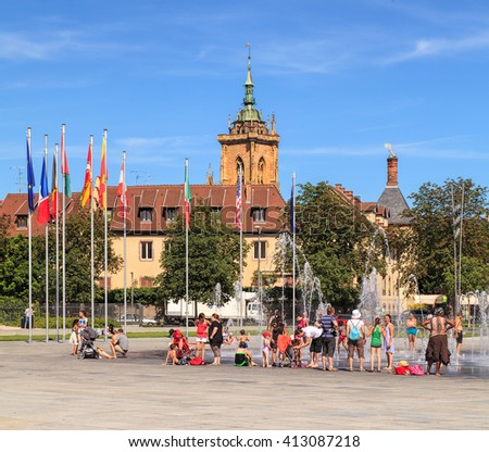 Colmar, France - 18 July, 2014: people at the fountain on Place Rapp square. Colmar is the third-largest commune of the Alsace region in north-eastern France, renowned for its well preserved old town.