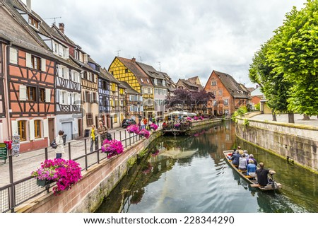 COLMAR, FRANCE - JULY 3, 2013: people visit town of Colmar, France. Colmar has thousands of small canals and therefore people call it little Venice. - stock photo