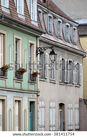 COLMAR, FRANCE - September 18, 2015: Old french traditional buildings with flowers in spots and shutters on windows in Colmar, vertical photo