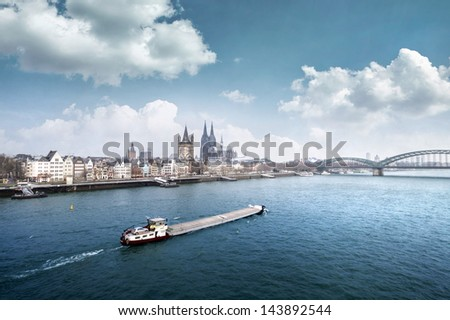 Cologne city line with cargo ship on rhine - stock photo