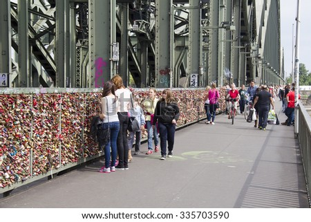 Cologne, Germany - August 27, 2013: Pedestrians on the footbridge along the Hohenzollern bridge with thousands of padlocks fastened to the railings on August 27, 2013 in Cologne, Germany - stock photo