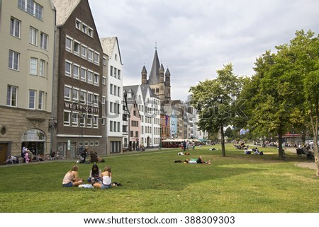 Cologne, Germany - August 27, 2013: People sitting on the grass at the riverfront in Cologne on August 27, 2013 in Cologne, Germany