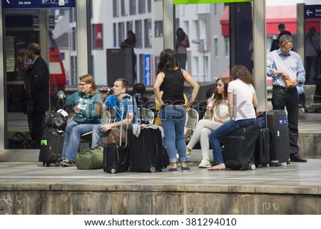 Cologne, Germany - August 30, 2013: Teenagers with luggage waiting for their train on a platform in the historic railway station of Cologne, Germany on August 30, 2013 - stock photo