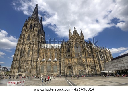 Cologne, Germany - August 27, 2013: Tourists walk around beneath Cologne's cathedral on August 27, 2013 in Cologne, Germany - stock photo