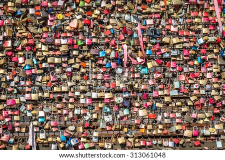 COLOGNE, GERMANY - JULY 31, 2015: Famous Hohenzollern Bridge with personal love padlocks, which have been places here since 2008. It is the most heavily used railway bridge in Germany - stock photo