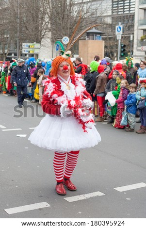 "Cologne, Germany - March 2nd, 2014: Carnival 2014. Women dressed as a clown at  carnival procession called ""Schull- und Veedelszoch"". Some spectators in the background, children inclusive."