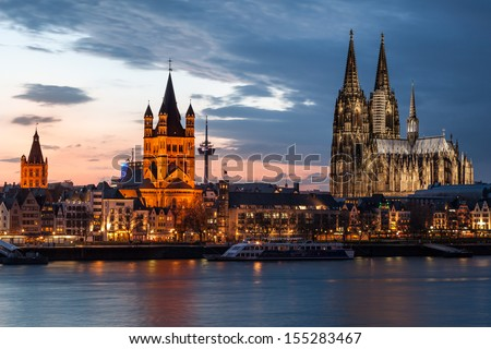 COLOGNE, GERMANY - MAY 25: Skyline cityscape after sunset on May 25, 2010 in Cologne, Germany. Illuminated, across the river Rhine, Cologne Cathedral stands tall next to the Great St. Martin Church.