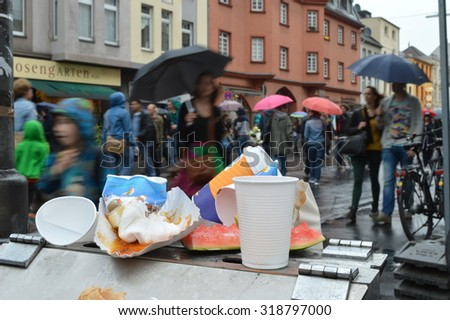 Cologne, Germany - May 31, 2015 - Waste as a mean problem in big cities and metropoles with people walking by during rain  - stock photo