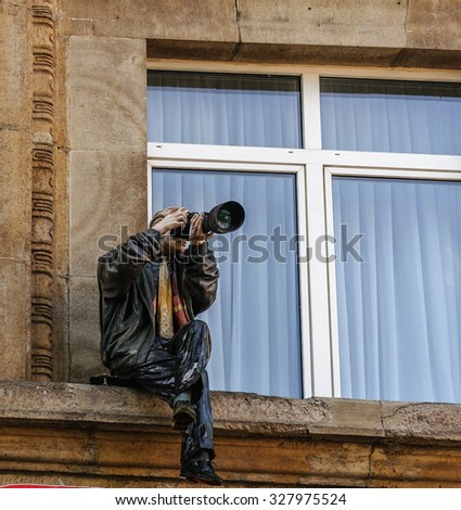 COLOGNE (KOLN), GERMANY - 2015 MAY 10: The statue of a photographer sitting on the ledge of the building on a square in Cologne (Koln), Germany